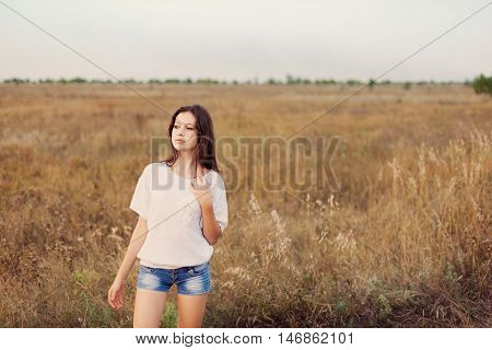 Young girl with long brown hair standing at the autumn meadow and looks thoughtfully left. Selective focus warm tinted.