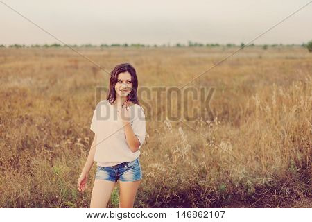 Young girl with long brown hair standing at the autumn meadow and smiling. Selective focus warm tinted.
