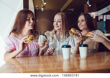 Three cheerful young girls eating fast food in a restaurant