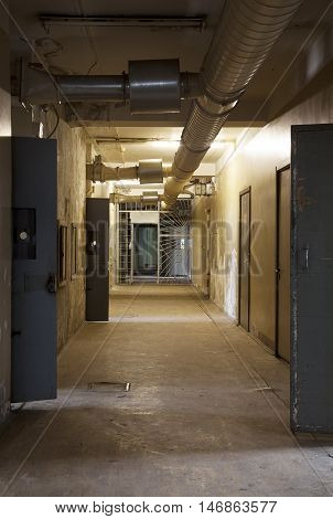 Corridor in an abandoned Penitentiary with open doors of prison cells