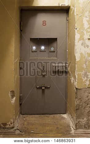 Light coming in through jail cell door at an abandoned prison jail