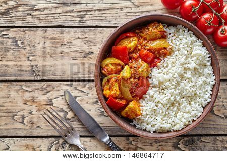 Chicken jalfrezi traditional homemade Indian spicy curry chilli meat with rice and vegetables healthy dietetic asian food in clay dish on vintage table background.