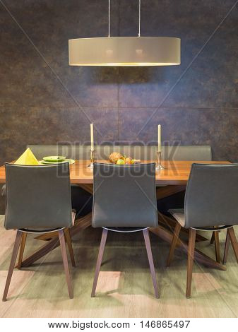sitting group of chairs and wooden table before structured wall