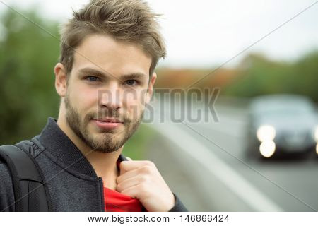 Young boy with cool fashion beard on handsome serious sexy face blue eyes brown hair in black and red clothes outdoor on road way background