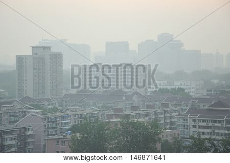 Apartment buildings rising up above the streets in the pollution filled air of Beijing China.