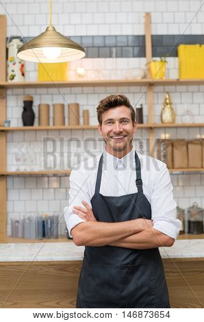 Portrait of a smiling young waiter leaning at counter of coffee shop with arms crossed. Successful owner with apron looking at camera. Young cook standing in kitchen. Small business concept.