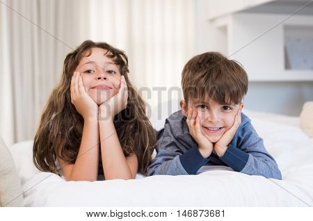 Children lying on front on bed. Cute little girl and boy lying on white bed and looking at camera. Happy smiling brother and sister in a playful mood after waking up in the morning.
