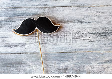 Cookie shaped as moustache. Biscuit on a stick. Taste and manners. Eat to become more manly.