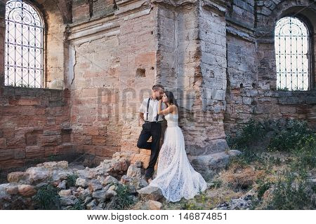Groom and fiancee in ancient building among ruins