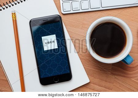 CHIANG MAI,THAILAND - May 15,2016: Photo of Apple iPhone with Uber application on the screen laying on the wooden table