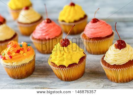 Bright-colored cupcakes. Baked desserts with icing. Recipe for great mood. Happiness has its taste.