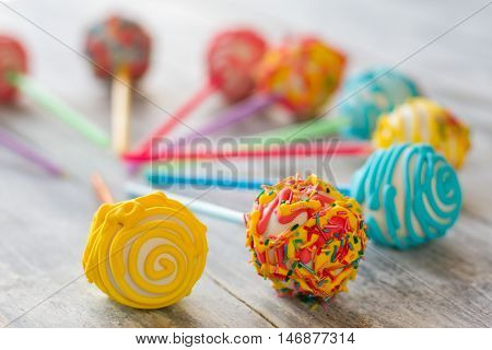 Colorful decorated candies. Ball-shaped sweets with glaze. Cake pops for birthday party. Confectionery made at order.