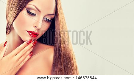 Girl with long straight hair and red lipstick and nails manicure