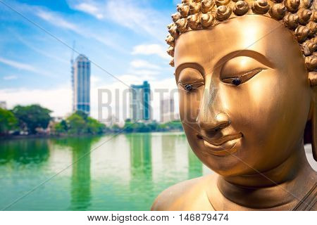 Buddha statue close up and Colombo in background
