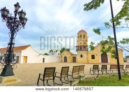 Santa Barbara church in Mompox Colombia with benches and and ornate streetlight