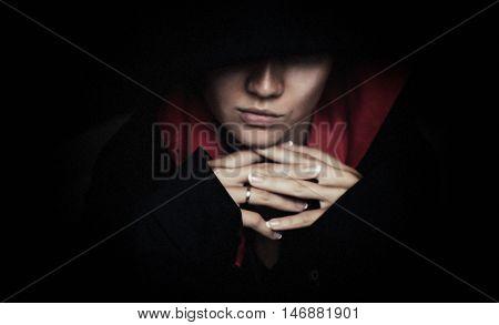 Portrait of mysterious woman in dark hood.