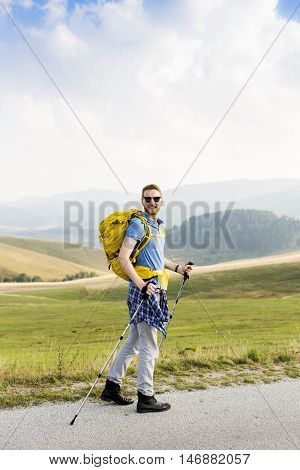 Young man hiking and walk on the mountain road