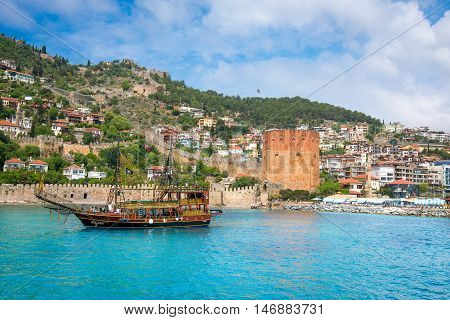 ALANYA TURKEY - MAY 3 2015: Unidentified tourists on old looking boat in front of Red Tower Alanya Turkey. Old looking ships are meant for tourist visits and parties.