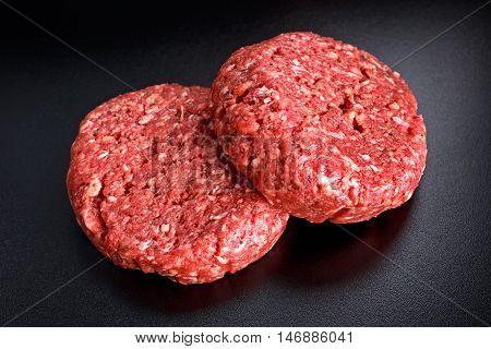 Home HandMade Raw Minced Beef steak burgers on black board.