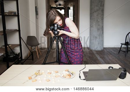 Woman photographing cookies set on white background. Food photographer working at studio with sweets.