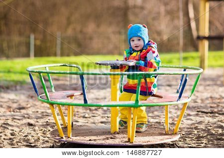 Little boy on a playground. Child playing outdoors in autumn. Kids play on school yard. Happy kid in kindergarten or preschool. Children having fun at daycare play ground. Toddler on a swing.