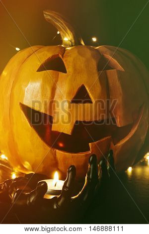 Close up of pumpkin with candle in black hand