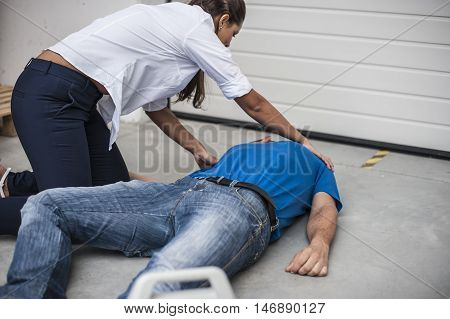 girl assisting an unconscious man with defibrillator