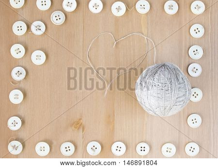 Vintage sewing buttons frame and ball of linen and heart shaped thread. Flat lay, top view. poster