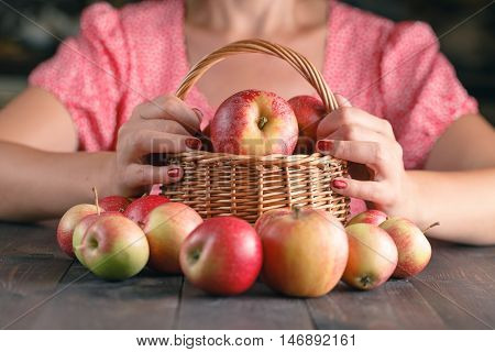 Woman  Is Holding A Wicker Basket Full Of Red Apples