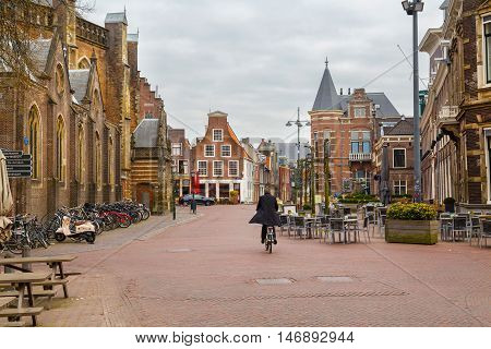Haarlem, Netherlands - April 2, 2016: Picturesque landscape with people, beautiful traditional houses and man riding bike, Haarlem, Holland