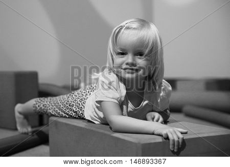Black And White Photo Of Cute Little Girl In Playing Room.