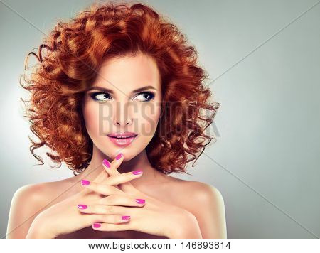 Beautiful model girl with curly red hair . Magenta manicure on nails .