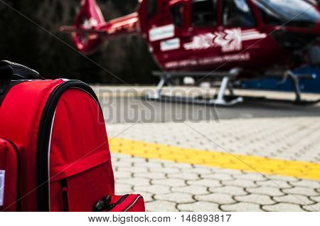 an emergency rucksack with medical devices and a rescue helicopter