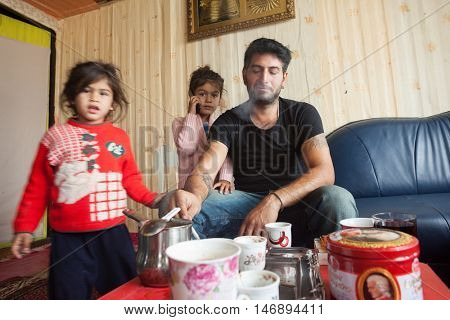 ZAGREB, CROATIA - OCTOBER 21, 2013: Roma man and his daughters at their home.