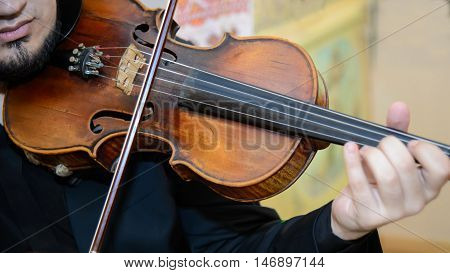 Violinist with a violin. Musician plays on an old wooden violin bow. Lovely classical music. An orchestral Symphony at the concert. Beautiful classical string instrument.