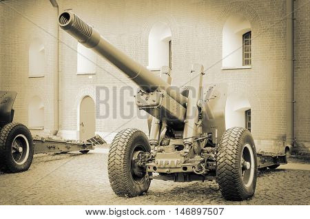 Old army artillery cannon background of fortress wall. Howitzer on wheels. Second world war. Old scratched photo. Retro toning.