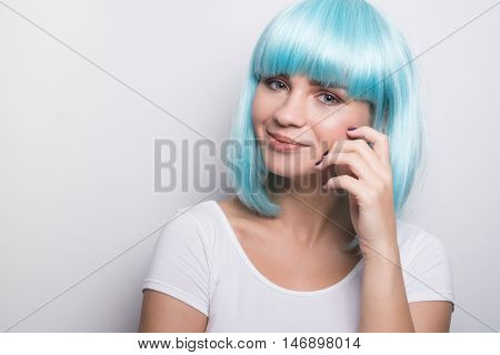 Cheeky young girl in modern futuristic style with blue wig smiling and looking into the camera over white wall background with copyspace