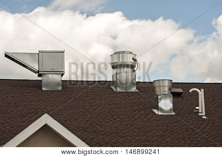 Sheet metal air ducts on rooftop of building on blue sky background