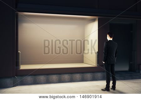 Back view of young businessman looking at empty clean storefront at night. Mock up 3D Rendering