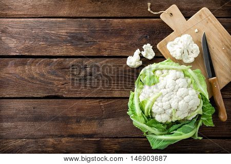 fresh raw cauliflower with leaves on wooden background