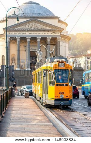Turin, Italy - June 10, 2016: Turin street view with Gran Madre church and old yellow tram. Morning life in Turin old town in Piedmont region in Italy