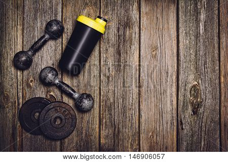 Old iron dumbbells or exercise weights with extra plates on an old wooden deck, floor or table. Image taken from above, top view. A lot of copy space around product
