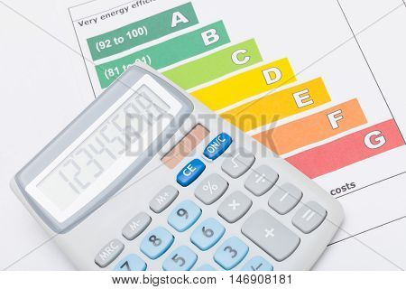 Calculator over energy efficiency chart - studio shot