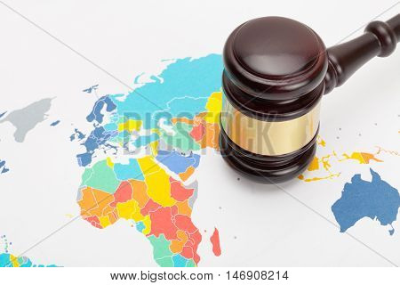 Judge's gavel over world map - studio shot