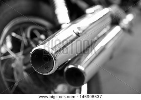 Chrome tailpipes of a motorcycle. Black and white image. Shallow DOF!!!