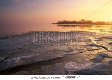 Winter landscape with frozen river and sunset sky.