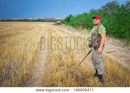 Hunter with a gun on the field