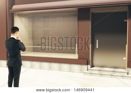 Thinking Businessman Looking At Storefront
