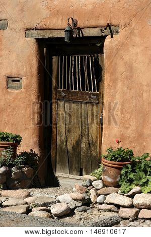 An old wooden door is set into an adobe wall in the Canyon Road Arts District, Santa Fe, New Mexico.