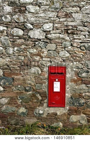 Traditional red postbox set in rural stone wall.